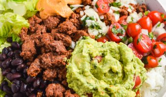 Loaded burrito bowls with a side of pico de gallo, fresh limes, and beer.