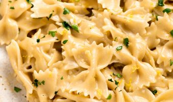 Close up image of lemon pasta with parsley on top.