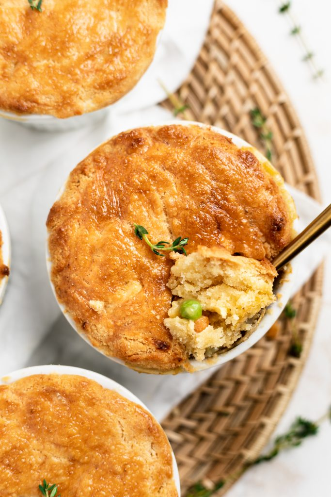 Overhead shot of three mini paleo chicken pot pies with a scoop taken out.