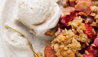 strawberry rhubarb crisp on a plate with a scoop of vanilla ice cream