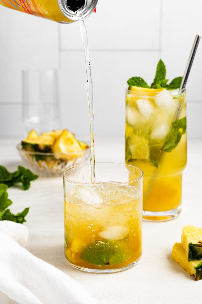 club soda being poured into a pineapple mojito