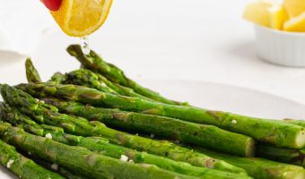 fresh lemon being squeezed over sous vide asparagus