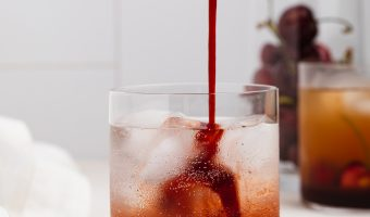 cherry cordial being poured into a glass of ice and sparkling water