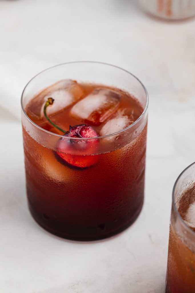 cherry cordial in a glass with sparkling water, ice, and a fresh cherry