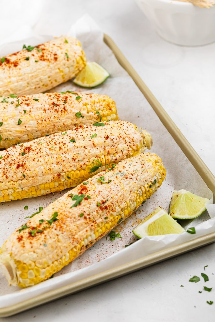 vegan elote on a baking sheet with fresh lime wedges