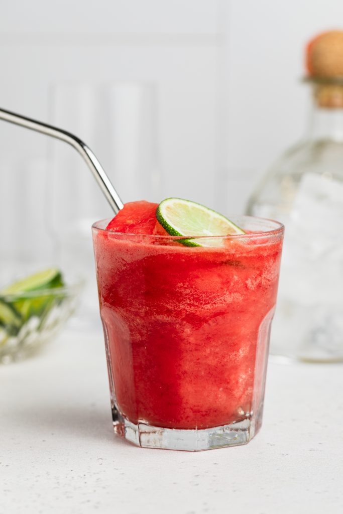 one glass of watermelon margarita with a bottle of tequila in the background