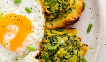 two zucchini hash browns on a plate with a fried egg on top
