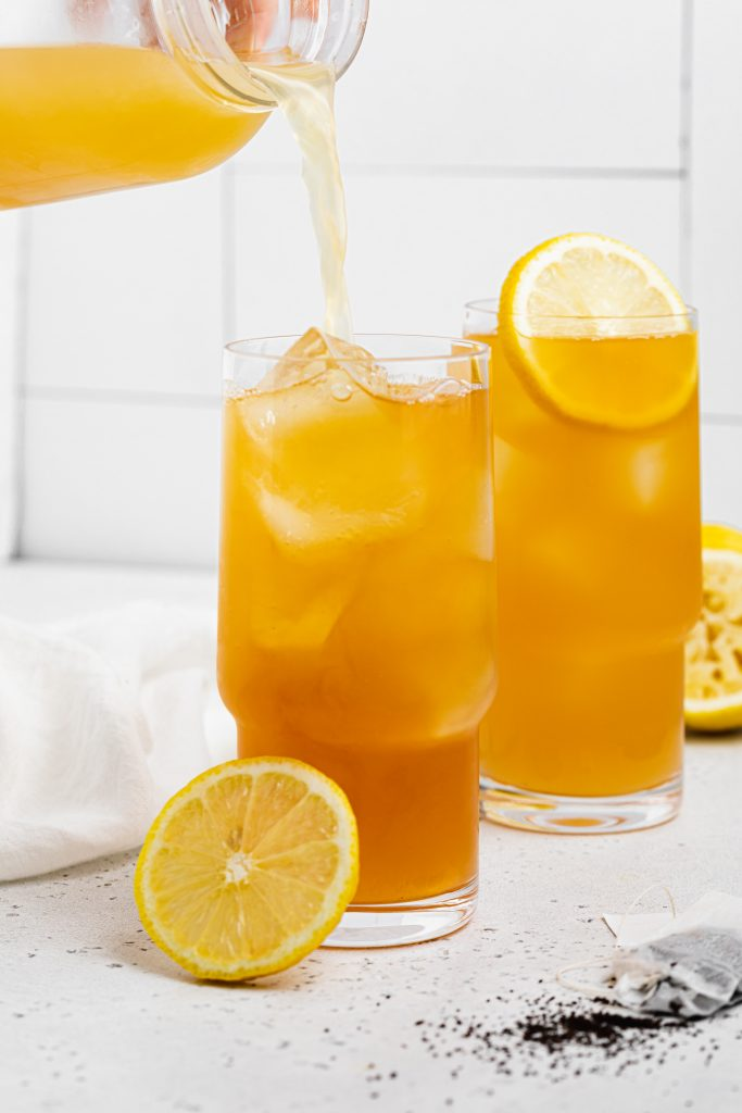 lemonade being poured into a glass of an arnold palmer drink with lemon slices on the side
