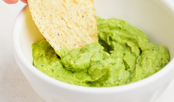 avocado crema being scooped from a bowl with a tortilla chip