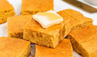 slices of gluten-free cornbread stacked on top of each other with butter and honey