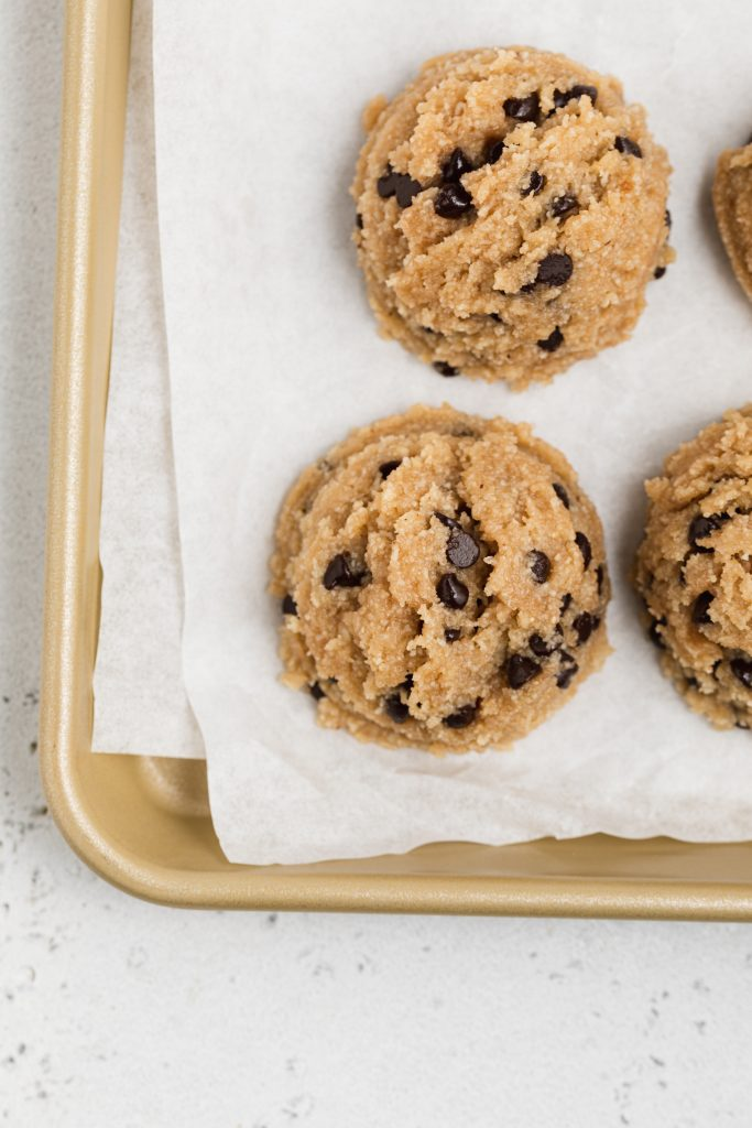 scoops of healthy cookie dough on a baking sheet