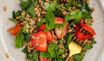 overhead image of strawberry spinach salad on a plate with a fork