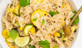 summer squash pasta on a plate with white wine, basil, and red pepper flakes on the side