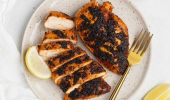 overhead image of blackened chicken on a plate with spices around the plate