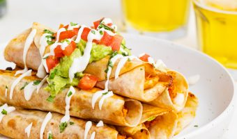 chicken taquitos on a plate with two glasses of beer and cilantro on the side