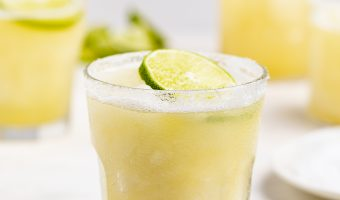 glasses of frozen margaritas with limes on top