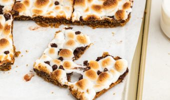 s'mores bars on a baking sheet with a glass of milk on the side