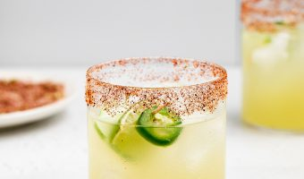 two spicy cucumber margaritas with spicy salt rim on the side